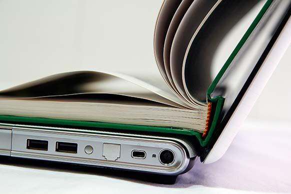 Für Geschäftsenglisch geöffnetes Buch über Laptop.