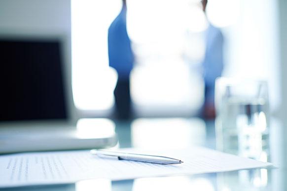 Inhouse Englischkurse im Firmen-Office. Im Hintergrund Manager im Rollenspiel. Business Dokumente, silberfarbener Stift auf Tisch.